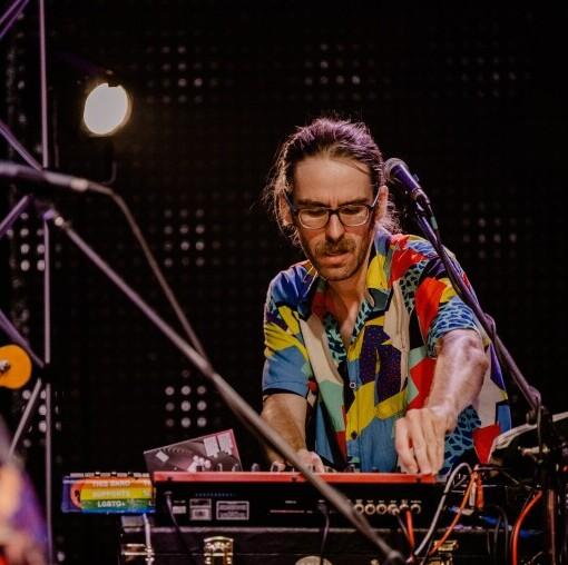Zdjęcie z koncertu grupy Javva. Na zdjęciu muzyk w kwiecistej koszuli, okularach, dłuższych włosach związanych z tyłu głowy. Nachyla się nad syntezartorem muzycznym, rękę trzyma na pokrętle.